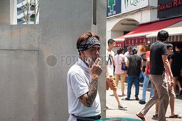 Singapur  Republik Singapur  Mann mit Mundschutz raucht eine Zigarette