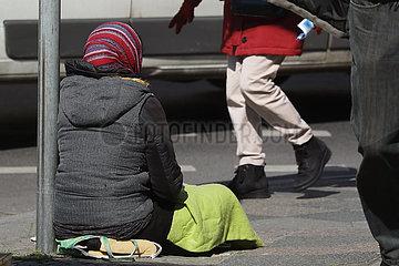 Berlin  Deutschland  Frau mit Kopftuch sitzt auf einer Strasse und bettelt