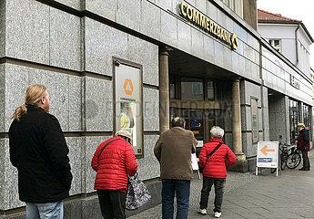 Berlin  Deutschland  Auswirkungen der Coronapandemie: Menschen stehen mit Abstand an einer Filiale der Commerzbank an