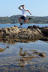 Saint-Marcouf  Frankreich  Junge macht einen Luftsprung ueber einem Felsen