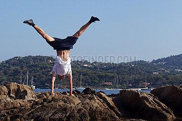 Saint-Marcouf  Frankreich  Junge macht einen Handstand auf einem Felsen