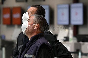 Berlin  Deutschland  Auswirkungen der Coronapandemie: Maenner mit Mund-Nasen-Schutz im Terminal des Flughafen Tegel