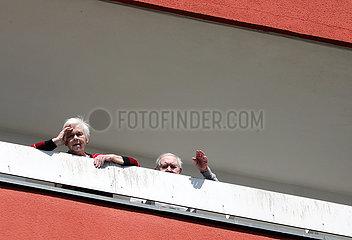 Berlin  Deutschland  Senioren stehen winkend auf ihrem Balkon