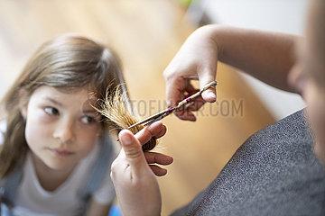 Mutter schneidet der Tochter die Haare