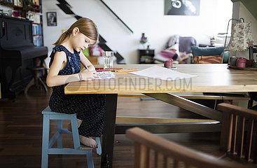 Kind schreibt oder malt in ein Heft