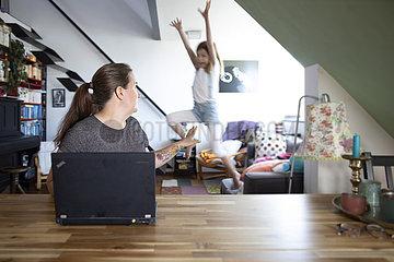 Frau mit Laptop am Esstisch