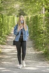 junge Frau mit Mundschutz  Spaziergang im Park  Muenchen  April 2020