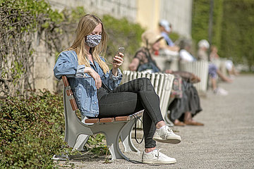 junge Frau mit Mundschutz  Parkbank  Muenchen  April 2020