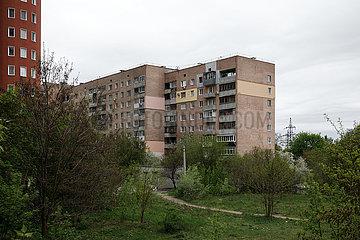 Wohngebaeude und Trampelpfad durch eine wilde Gruenflaeche in Charkiw