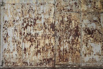 Abgeblaetterte Farbe und Rost auf einer Metalltuer an einem Fabrikgebaeude in Charkiw