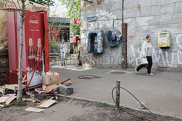 Heruntergekommene Strassenecke mit oeffentlichen Telefonen und Cola-Automat in Kiew