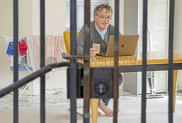 Mann im Homeoffice  waehrend Corona Lockdown  hinter Gittern  Humor  Muenchen  April 2020