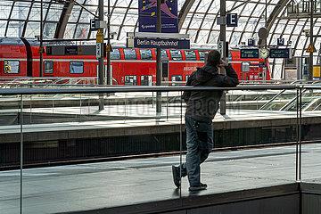 Berlin waehrend der Ausgangsbeschraenkung: Einzelner Mann wartet im Berliner Hauptbahnhof