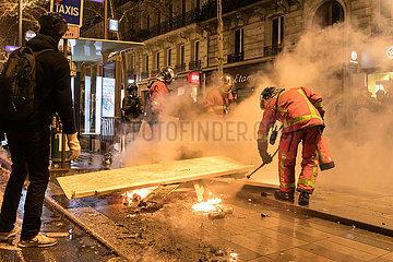 Feuerwehrmann loescht die brennende Strassenbarrikade waehrend der Demonstration