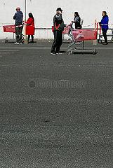Deutschland  Bremen - Warteschlange wegen Corona: Kunden mit Einkaufswagen vor einem Baumarkt