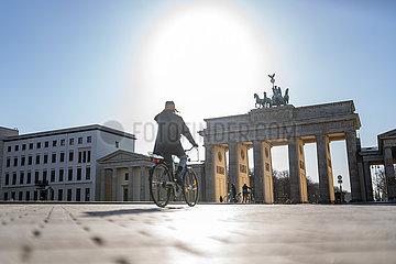 Berlin waehrend der Ausgangsbeschraenkung: Fahrradfahrerin faehrt auf dem leeren Pariser Platz