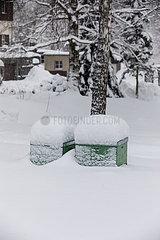 Tief verschneite Bienenkaesten bei einem Imker im Saechsischen Erzgebirge