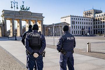 Berlin waehrend der Ausgangsbeschraenkung: Polizisten stehen auf dem sonst menschenleeren Pariser Platz am Brandenburger Tor