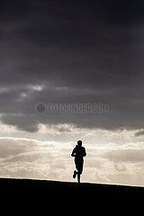 Jogger laeuft ueber den Deich am Neuharlingersiel waehrend der Ausgangsbeschraenkung