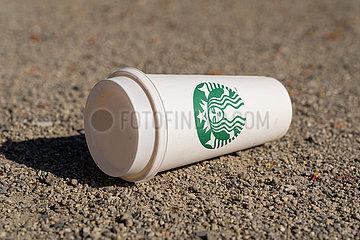 Leerer Becher der Firma Starbucks liegt auf dem Boden