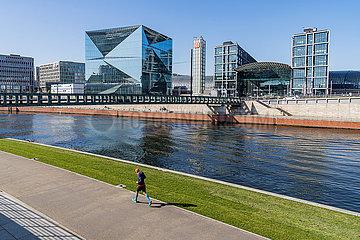 Berlin waehrend der Ausgangsbeschraenkung: Jogger laeuft an der sonst menschenleeren Uferpromenade der Spree entlang