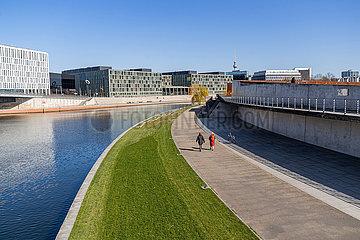 Berlin waehrend der Ausgangsbeschraenkung: Spaziergaenger laufen auf der sonst menschenleeren Uferpromenade an der Spree entlang