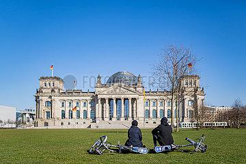 Berlin waehrend der Ausgangsbeschraenkung: Ein Paerchen sitzt gemeinsam vor der menschenleeren Wiese am Reichstag