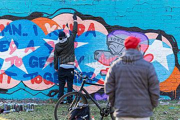 Ein Graffitikuenster bemalt eine Wand