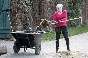 Neuenhagen  Stallmitarbeiterin saeubert den Weg vor dem Stall