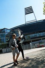 Deutschland  Bremen - Zwei Jungen mit Fussball vor dem Weserstadion des SV Werder Bremen