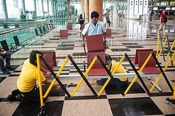 Singapur  Republik Singapur  Arbeiter entfernen am Flughafen Changi Sitze als Massnahme zum Safe Distancing