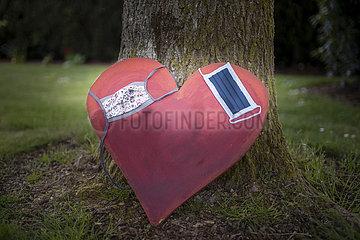 Herz mit zwei Masken lehnt an einem Baum