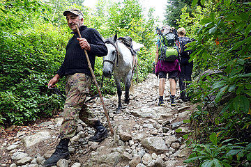 Mazeri  Georgien  Mann ist zu Fuss mit seinem Pferd in den Bergen unterwegs