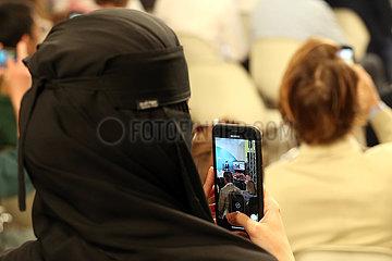Riad  Saudi-Arabien  Frau im Niqab filmt eine Veranstaltung mit ihrem Mobiltelefon