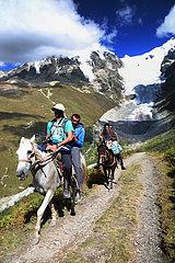 Adishi  Georgien  Wanderer reiten mit Einheimischen auf deren Pferden eine Bergstrasse am Tetnuldi entlang