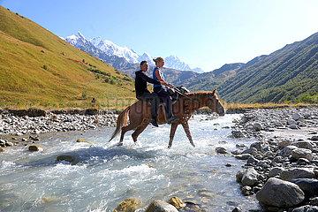 Adishi  Georgien  Mann und Frau ueberqueren auf einem Pferd einen Gletscherfluss am Tetnuldi