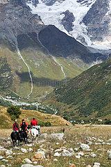 Ushguli  Georgien  Touristen machen im Gebirge einen Ausflug zu Pferde