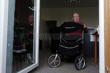 Berlin  Deutschland  Senior sitzt mit seinem Rollator an der geoeffneten Balkontuer seiner Wohnung