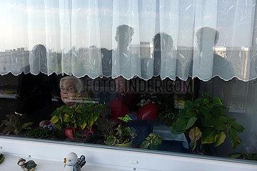 Berlin  Deutschland  Seniorenpaar kann in Zeiten der Coronapandemie Familienangehoerige nur getrennt durch eine Fensterscheibe sehen