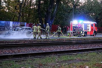 Berlin  Deutschland  Feuerwehrmaenner haben ein brennendes Auto auf einer Strasse geloescht