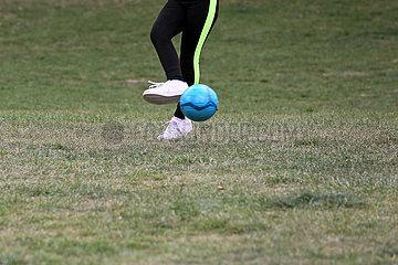 Berlin  Deutschland  Detailaufnahme: Jugendliche kickt einen blauen Fussball