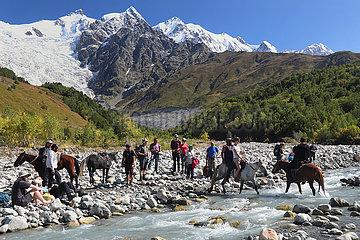 Adishi  Georgien  Wanderer werden von Einheimischen auf Pferden ueber einen Gletscherfluss am Tetnuldi gebracht