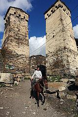 Ushguli  Georgien  Junge reitet auf seinem Pferd an den historischen Wehrtuermen des Dorfes vorbei