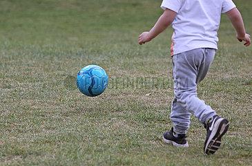 Berlin  Deutschland  Detailaufnahme: Junge spielt Fussball