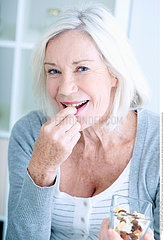 ELDERLY PERSON EATING DRIED FRUIT