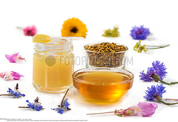 Variety of raw organic honey bee products board surrounded by flowers on white background