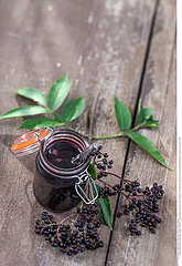 Elderberry Jam. Jar of homemade elderberry confiture and fresh fruits on old wooden background