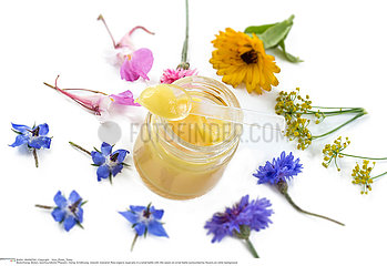 Raw organic royal jelly in a small bottle with litte spoon on small bottle surrounded by flowers on old white background.