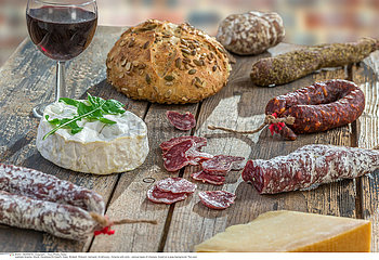 French snacks with wine - various types of cheeses  bread   dry saussages  charcuterie  red vine on a gray background. Top view.