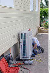 Energy saving. plumber at work installing a circulation heat Pump